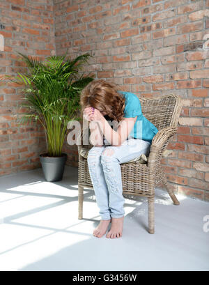 woman sitting on the chair in depression - Stock Photo