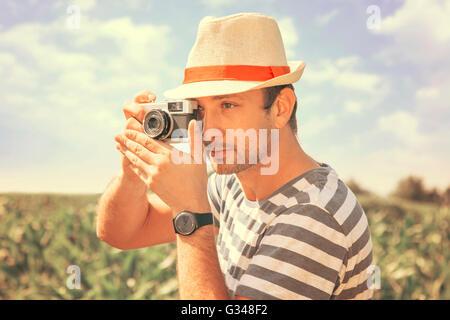 Man taking photo with retro camera - Stock Photo