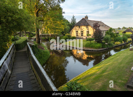 Giethoorn, Netherlands. Boat in the Dorpsgracht or Village Canal with converted farmhouse on island with private - Stock Photo