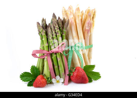 Bundle of green and white asparagus with strawberry. Fresh healthy vegetables on white background. - Stock Photo