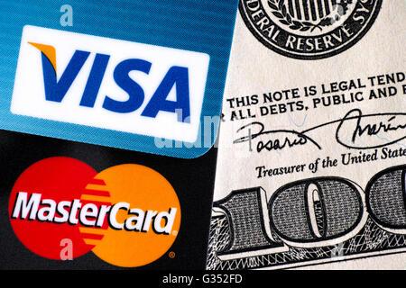 Tambov, Russian Federation - April 02, 2016 Visa and MasterCard logo on credit cards on one hundred dollar bill. - Stock Photo