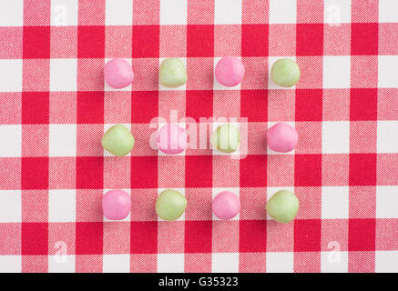 Candy on a red and white chequered tablecloth - Stock Photo