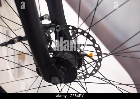 Front wheel hub of bicycle with hydraulic disk brake closeup shot - Stock Photo