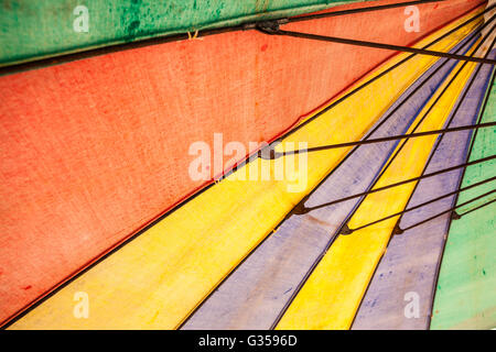 a colorful rainbow colored beach umbrella seen from below - Stock Photo