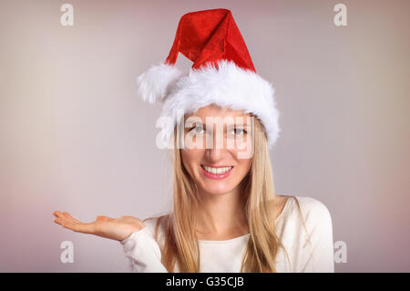 Beautiful woman with a Santa hat gestures palm up. Smiling Christmas girl - Stock Photo