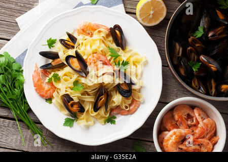 Pasta with seafood on wooden table. Mussels and prawns. Top view - Stock Photo