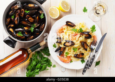 Pasta with seafood and white wine on wooden table. Mussels and prawns. Top view