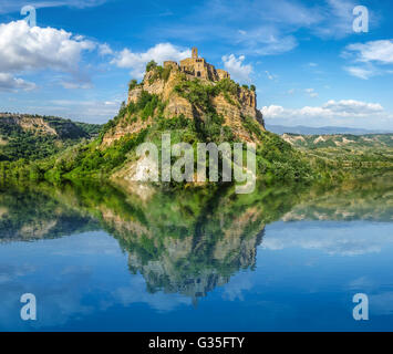 Beautiful panoramic view of historic castle on famous rock reflecting in crystal clear lake on a sunny summer day - Stock Photo