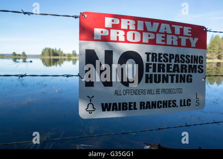 No trespassing sign on fence at Peterson Creek Reservoir in Oregon's Ochoco Mountains. - Stock Photo
