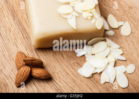 Whole food, good for health. Marzipan paste sliced blanched almonds and seeds on wooden kitchen board background - Stock Photo