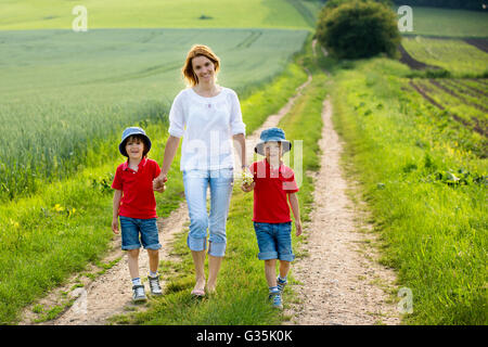 Young mother with her two children in a spring blooming field on sunset, rural scene - Stock Photo