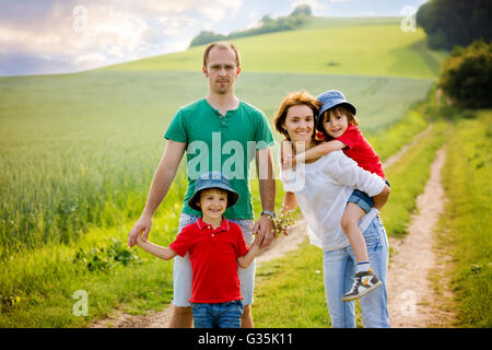 Family of four in field on a rural path, springtime, having fun together - Stock Photo