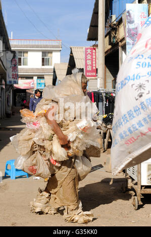 CHINA Yunnan, Yongningxiang, market, mentally disturbed waste picker dressed in plastic foil garbage - Stock Photo