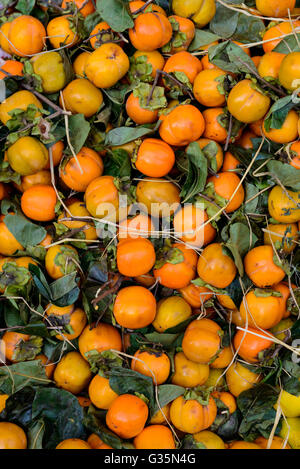 Kaki fruits for sale on a market stall - Stock Photo