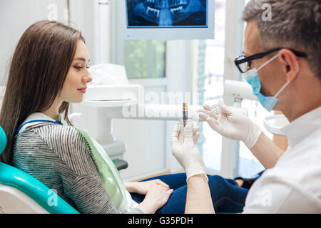 Male dentist showing his female patient a dental implant in clinic - Stock Photo