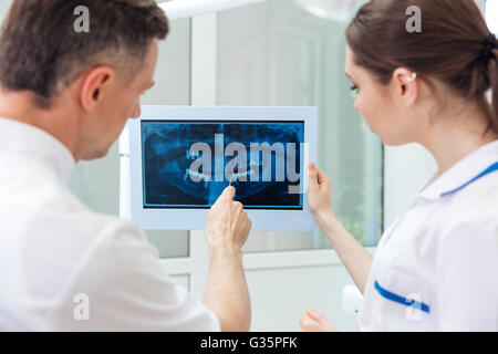 Male dentist showing something on the computer monitor to female nurse at clinic - Stock Photo
