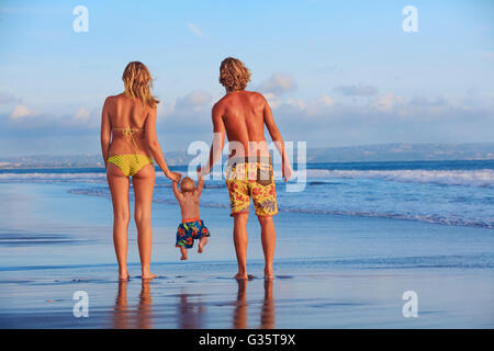 Happy family - father, mother, baby son hold hands, swim with fun, walk along sunset sea surf on black sand beach. - Stock Photo