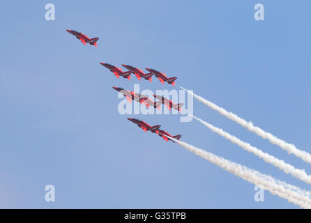 The RAF Red Arrows aerobatic team flying in formation against a blue sky, Duxford Airshow, UK; leadership concept - Stock Photo