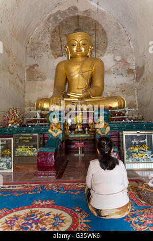 Woman prying in the front of an ornate statue of Buddha in temple, Old Temple Architecture, Myanmar, Burma, South - Stock Photo