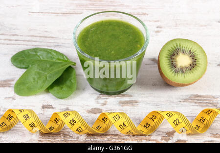Fresh ingredients and green nutritious cocktail from spinach with tape measure on old wooden background, slimming - Stock Photo