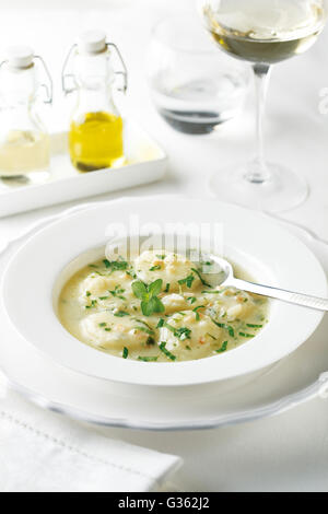 Boiled potatoes in a cream sauce with parsley and almonds - Stock Photo