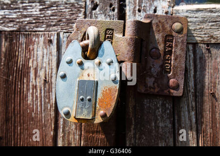 Rusting Locked Padlock On Weathered Old Wooden Doors - Stock Photo
