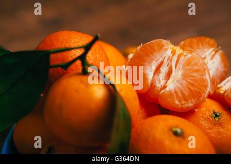 fresh peeled  tangerine segments close up on a background of orange mandarins - Stock Photo