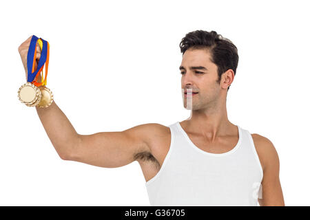 Athlete posing with gold medals - Stock Photo