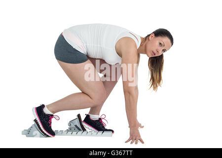 Confident athlete woman running from starting blocks - Stock Photo