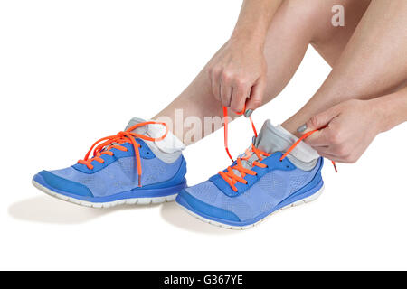 Athlete woman tying her running shoes - Stock Photo
