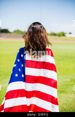 Female athlete wrapped in american flag - Stock Photo