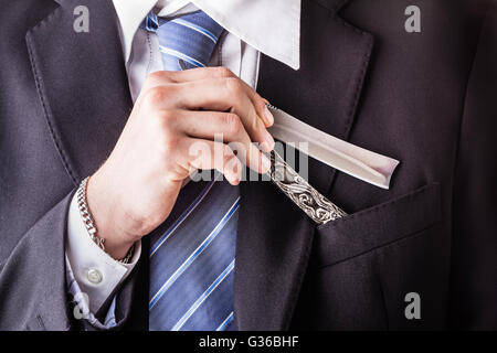 a young and handsome businessman holding a cut-throat razor isolated over a white background - Stock Photo