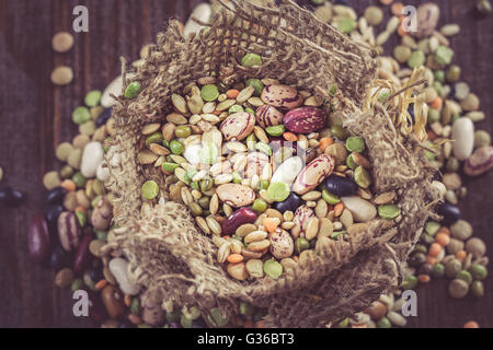 Mixed dried legumes and cereals in small burlap bag on dark wooden background - Stock Photo
