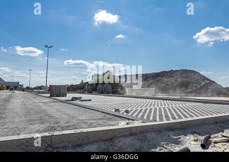 View at new parking place. Dumper truck is going over construction site in background. - Stock Photo