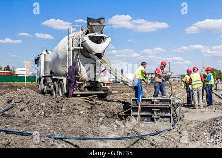 Workers at building site are pouring concrete in reinforced mold. - Stock Photo