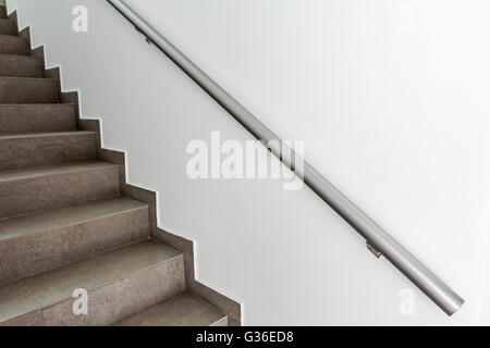 Stairway with metallic banister in a new modern building. Every building is required to have emergency stairways - Stock Photo