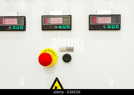 Electrical control panel containing has a digital temperature gauge with warning sticker and an emergency shutdown - Stock Photo