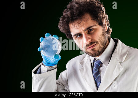 a young handsome doctor or researcher with a white lab coat holding an empty petri dish - Stock Photo