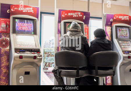 Man and woman at Roulette gaming machine (FOBT fixed odds betting terminal) in Ladbrokes Bookmakers in England, - Stock Photo