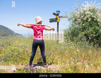 Female hiker on footpath through wildflower meadow in mountains of Gran Canaria. Canary Islands, Spain - Stock Photo
