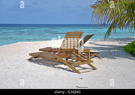 Two beach chairs under palm tree leaves - Stock Photo