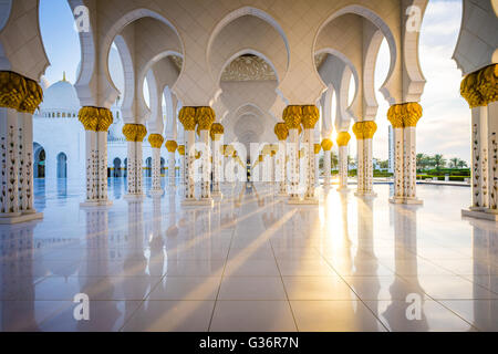 A View down a colonnade in the Sheikh  Zayed Grand Mosque in Abu Dhabi at Sunset - Stock Photo