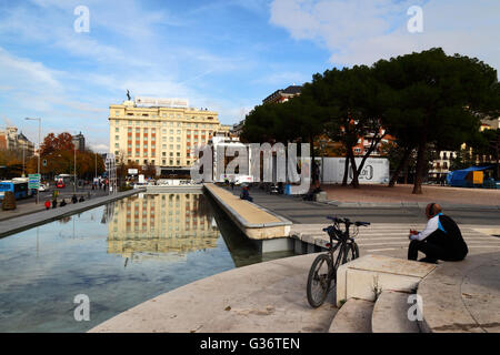Man wearing headphones sitting next to bicycle in Jardines del Descubrimiento, Plaza de Colon, Madrid, Spain - Stock Photo