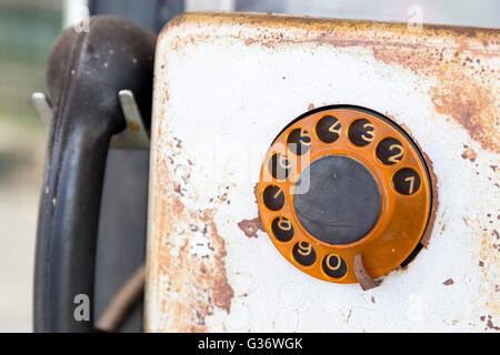 Rusty old vintage rotary pay phone for public use. Old pay telephone with coin slots on a wall. - Stock Photo