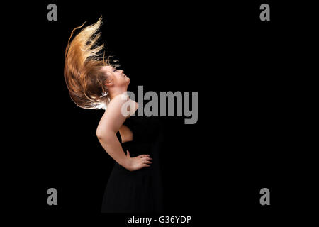 A teenage girl with beautiful, long, blond hair flips her hair against a black, background.  Her hair is back lit. - Stock Photo