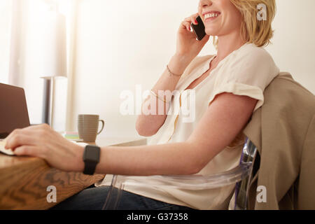 Cropped image of happy woman sitting at a table and talking on mobile phone, she is working at home. - Stock Photo