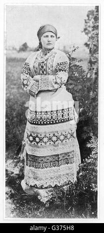 A Russian peasant girl in a  highly decorative full-length dress        Date: circa 1905 - Stock Photo