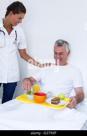 Female doctor talking to senior man while having breakfast - Stock Photo
