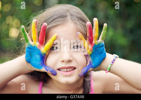 Smiling Little Girl looking at camera and showing her painted hands