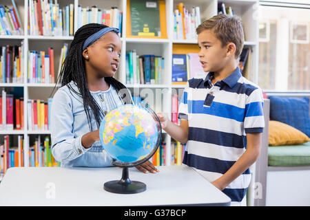 School kids discussing with each other in library with globe on table - Stock Photo